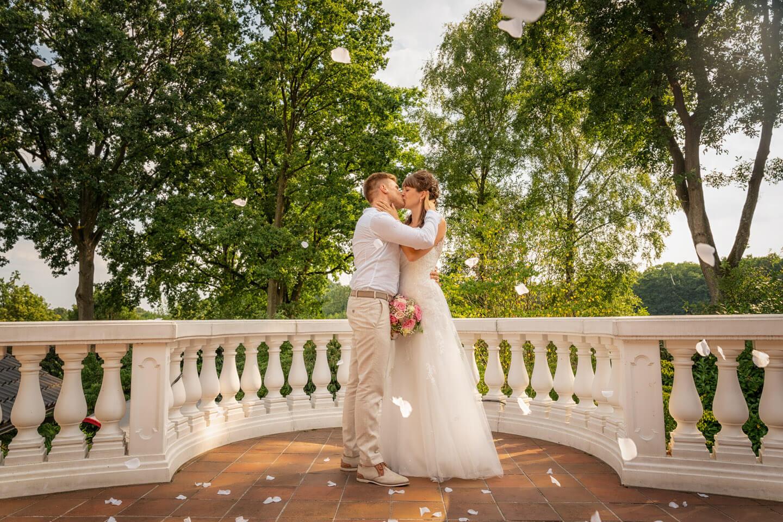 Weiße Rosenblättervregnen auf das Brautpaar
