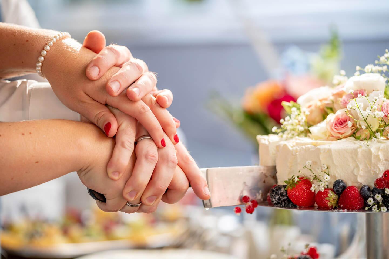 Anschnitt der Hochzeitstorte. Wer hält die Hand oben?