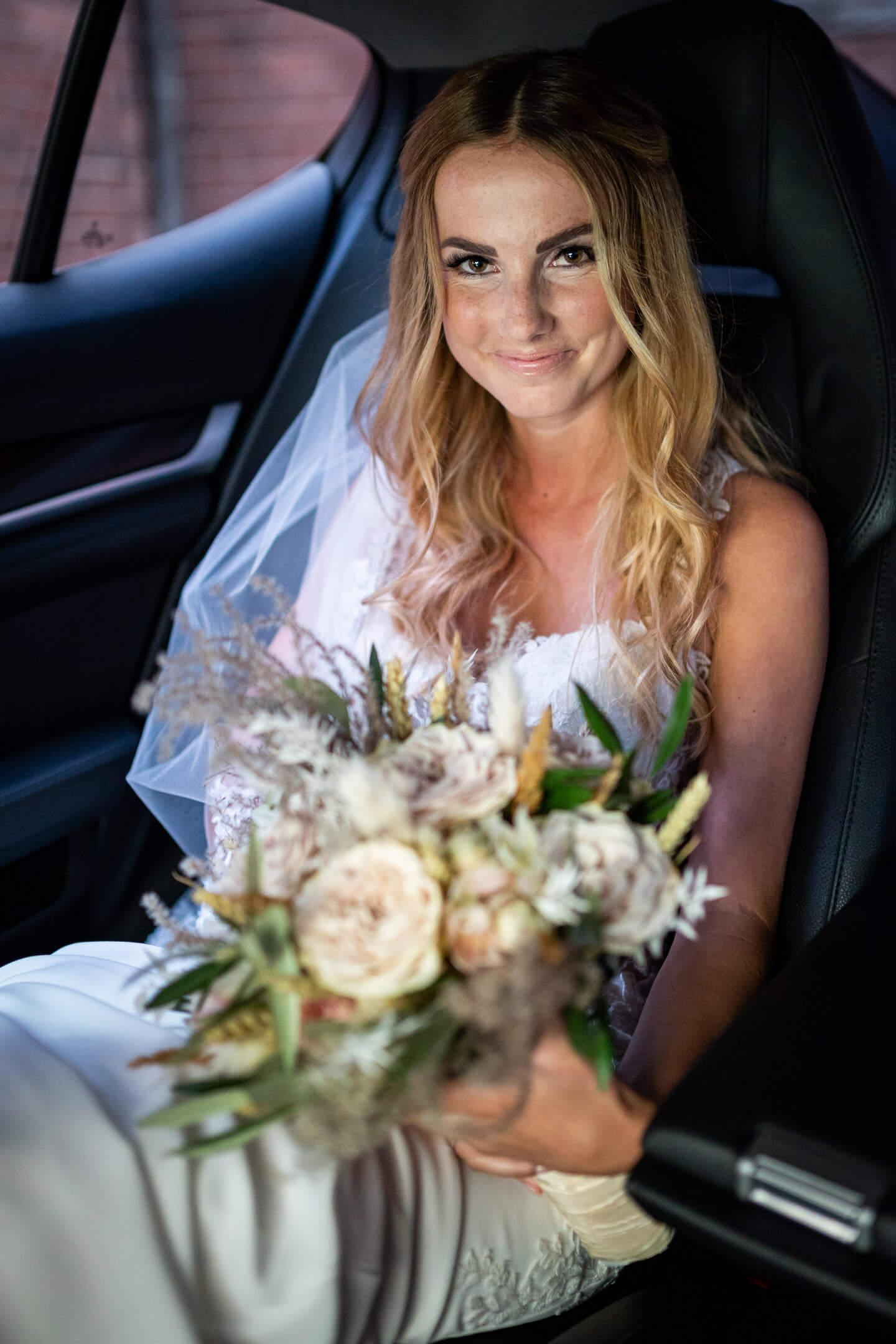 Braut sitz mit ihrem Brautstrauss im Auto und wartet auf die Hochzeit in Buxtehude