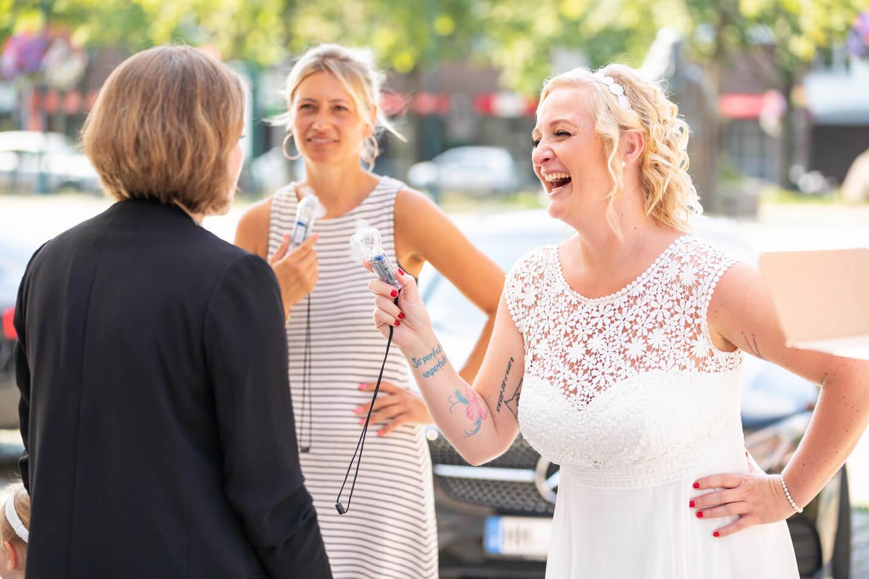 Braut mit Trauzeugin und Standesbeamtin mit Miniventilator an einem heißen Sommertag