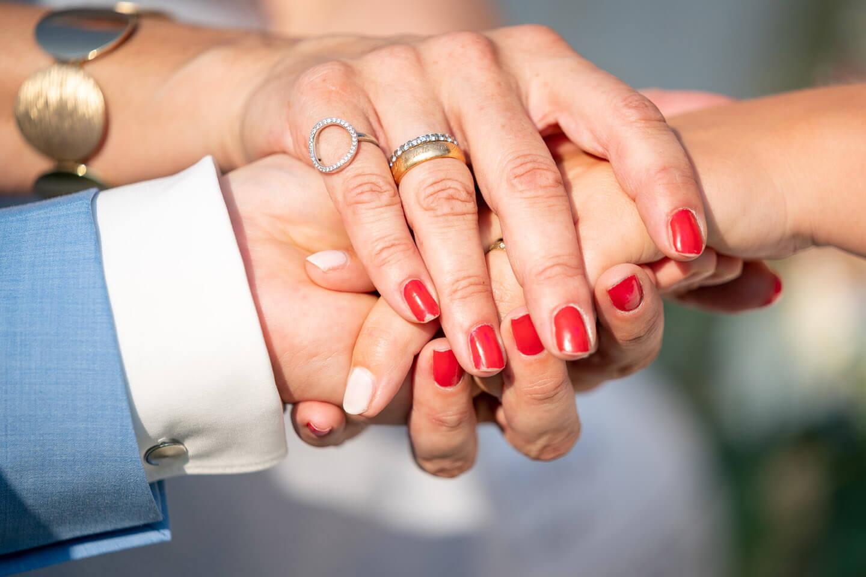 Hände des Hochzeitspaars und der freien Rednerin