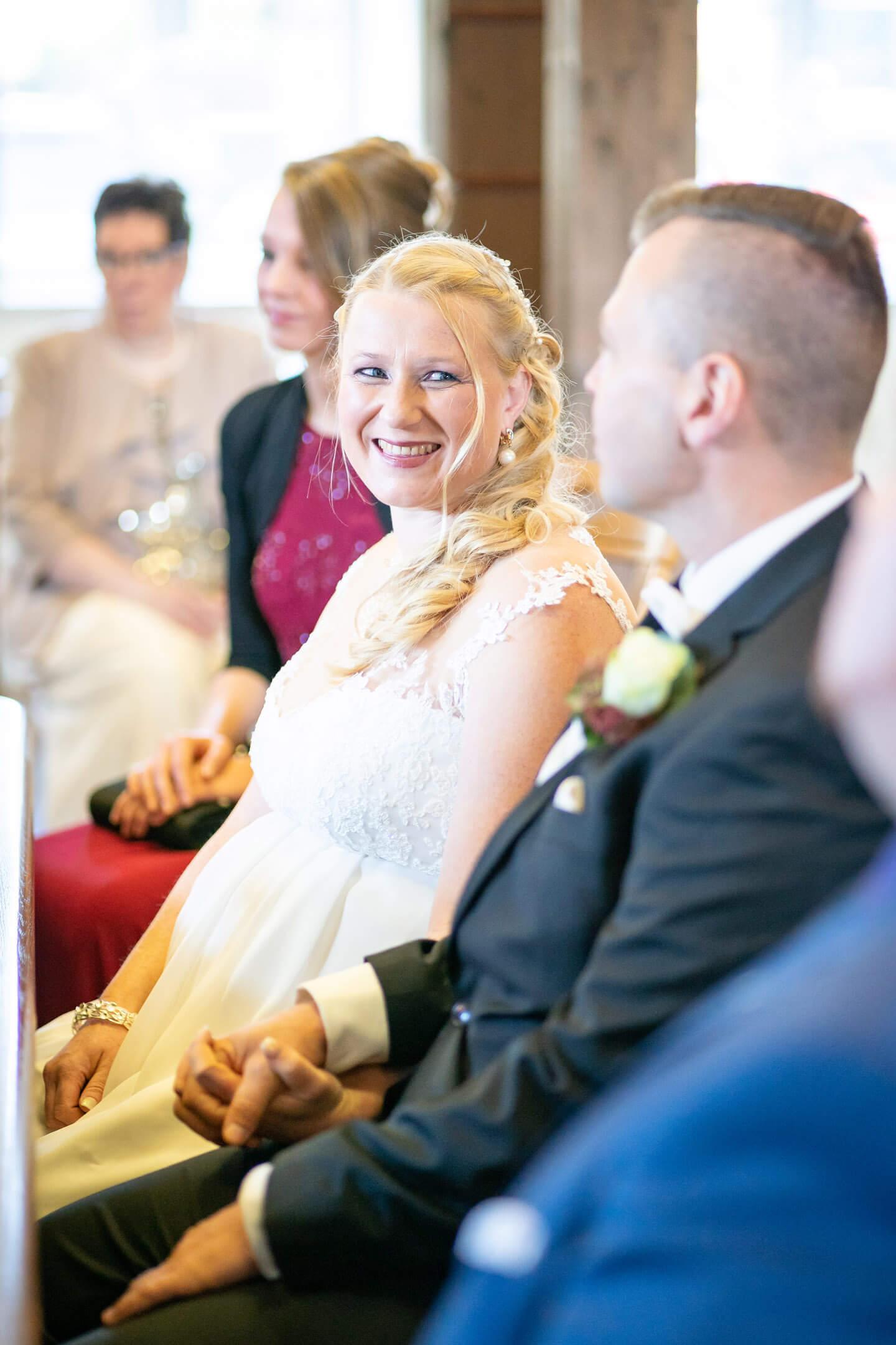 Braut blickt Bräutigam bei der Trauung lachend an.