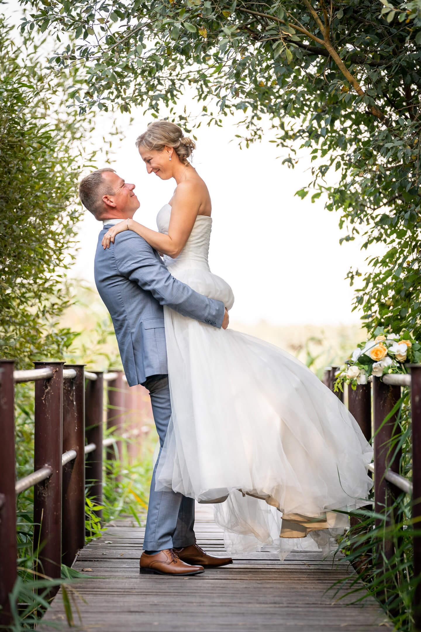 Auf Händen getragen: Bräutigam hebt seine Braut hoch.