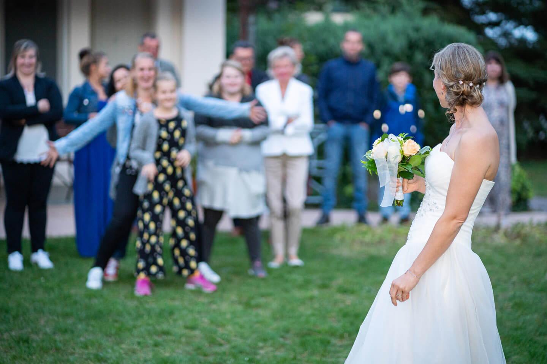 Kurz vor dem Brautstrausswurf: Braut blickt sich um.
