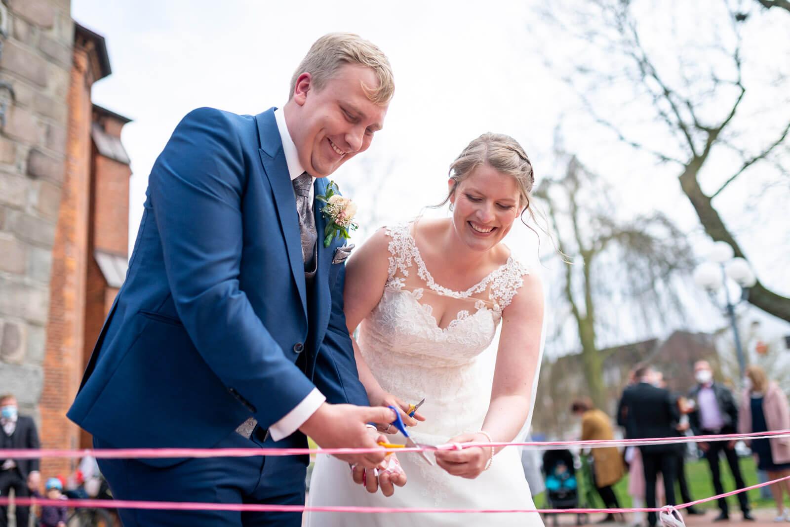 Brautpaar durchschneidet Bänder vor der Kirche