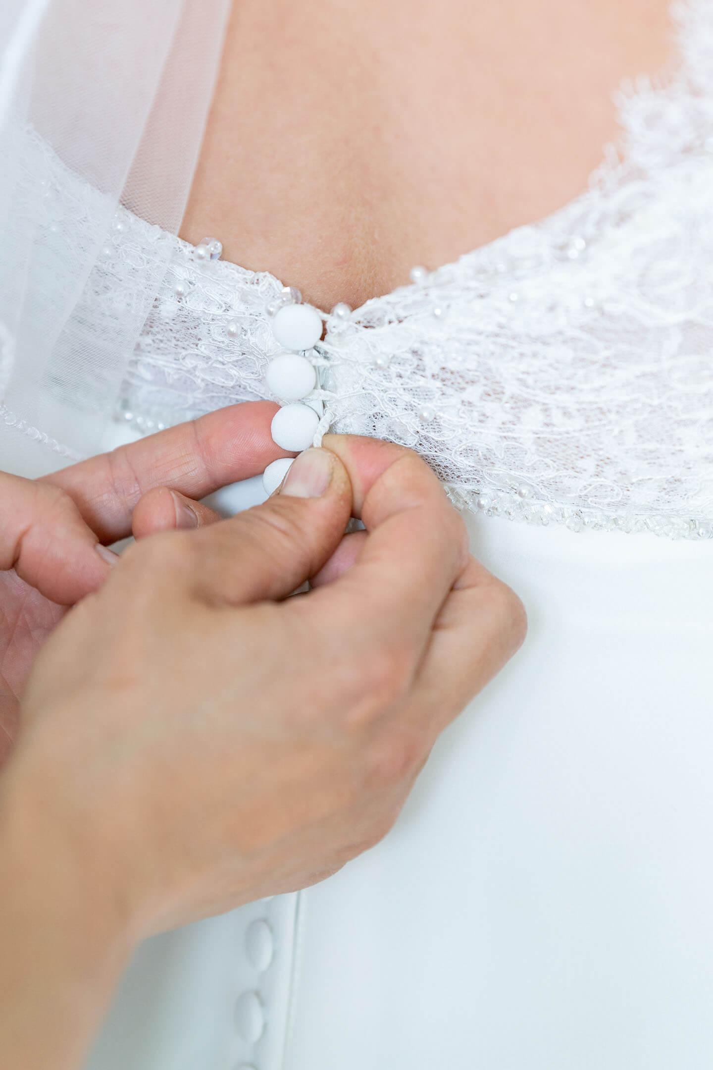 Brautkleid wird zugeknöpft.