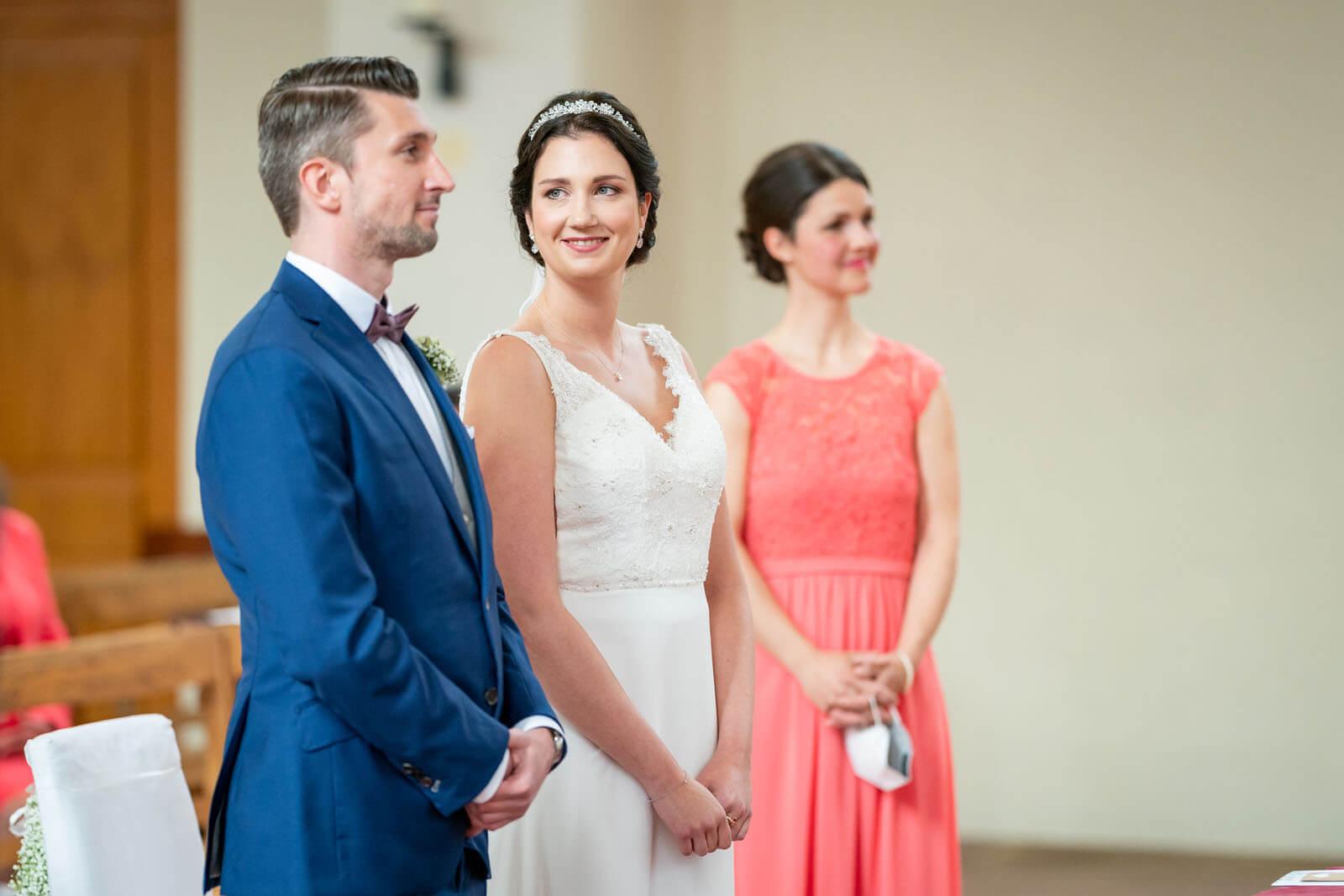 Brautpaar und Trauzeugin vor dem Altar.