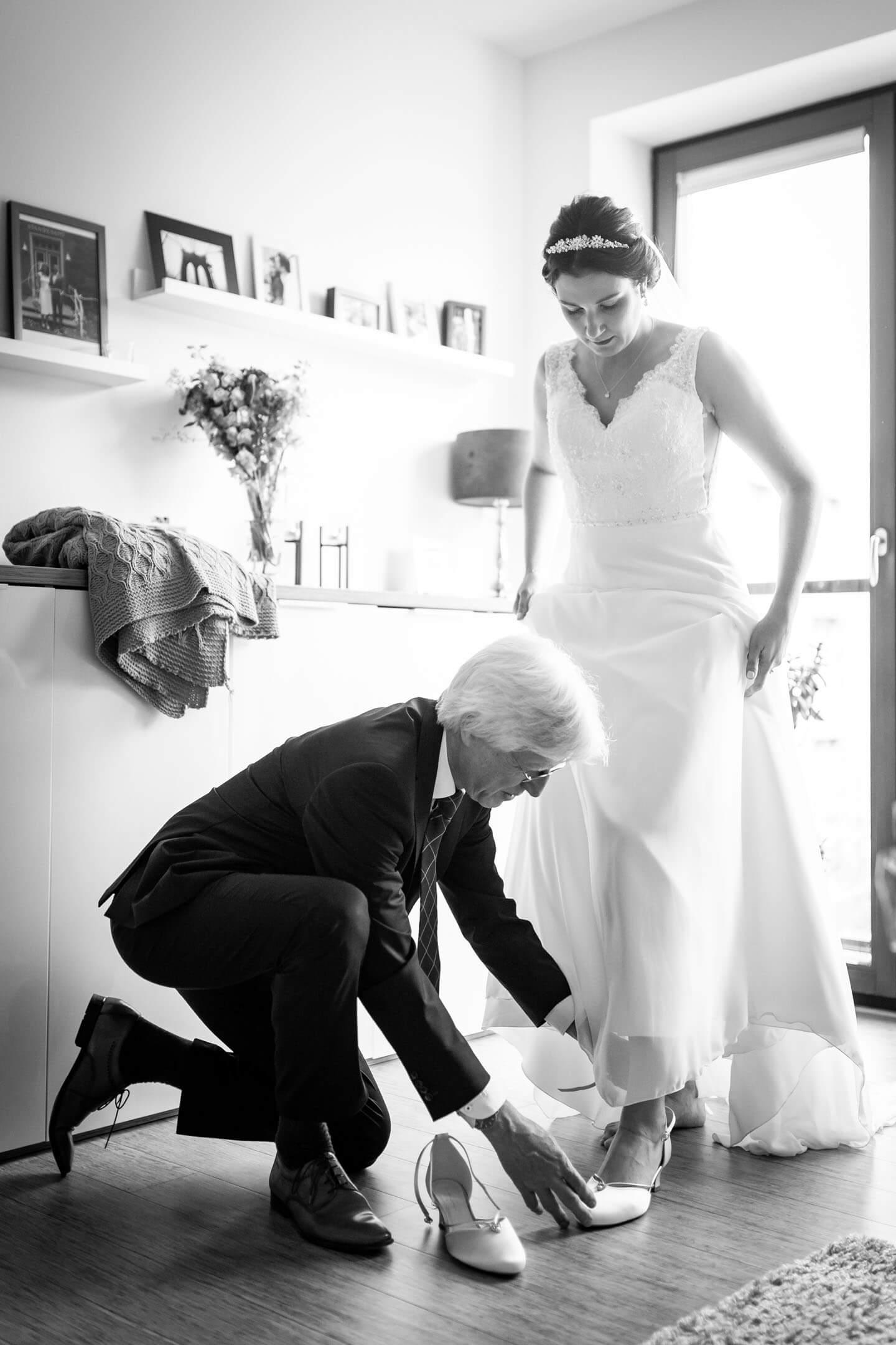 Brautvater zieht der Braut die Hochzeitsschuhe an.