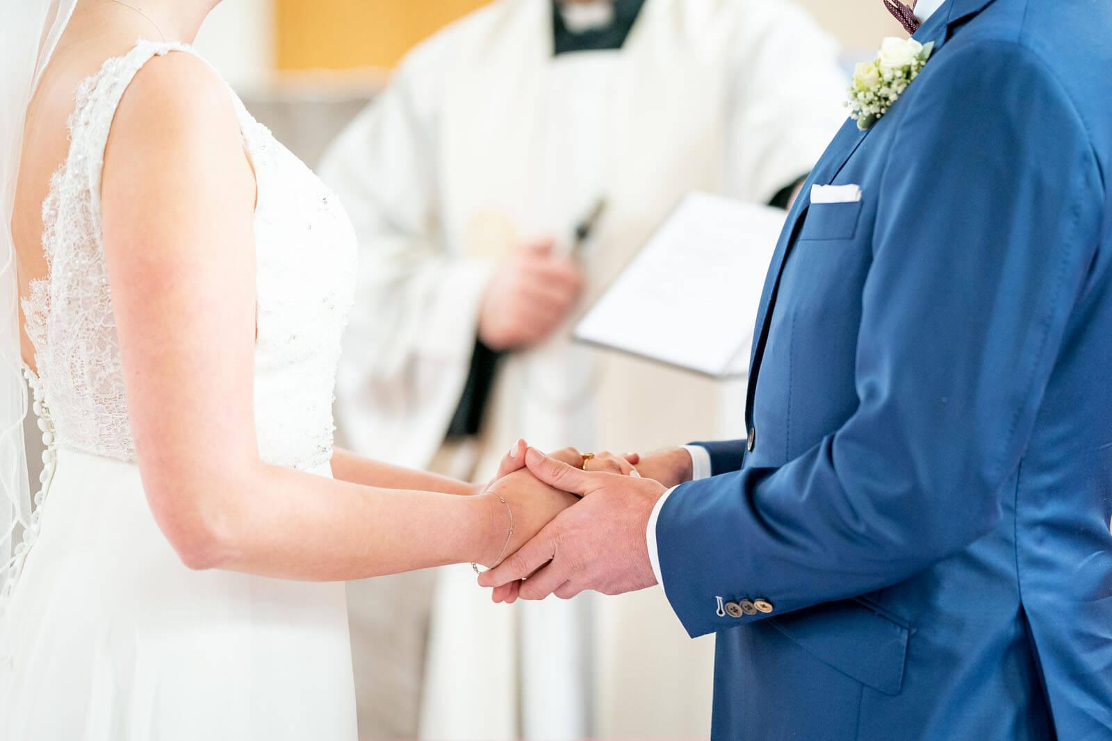 Brautpaar hält sich am Atar die Hände. Fotograf Florian Läufer aus drückte im richtigen Moment auf den Auslöser.