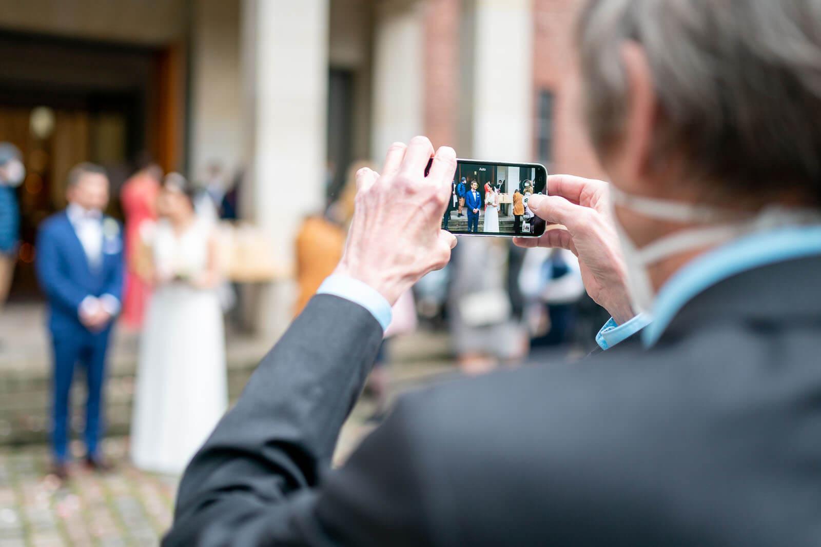 Handyfoto vom Brautpaar vor der Kirche.
