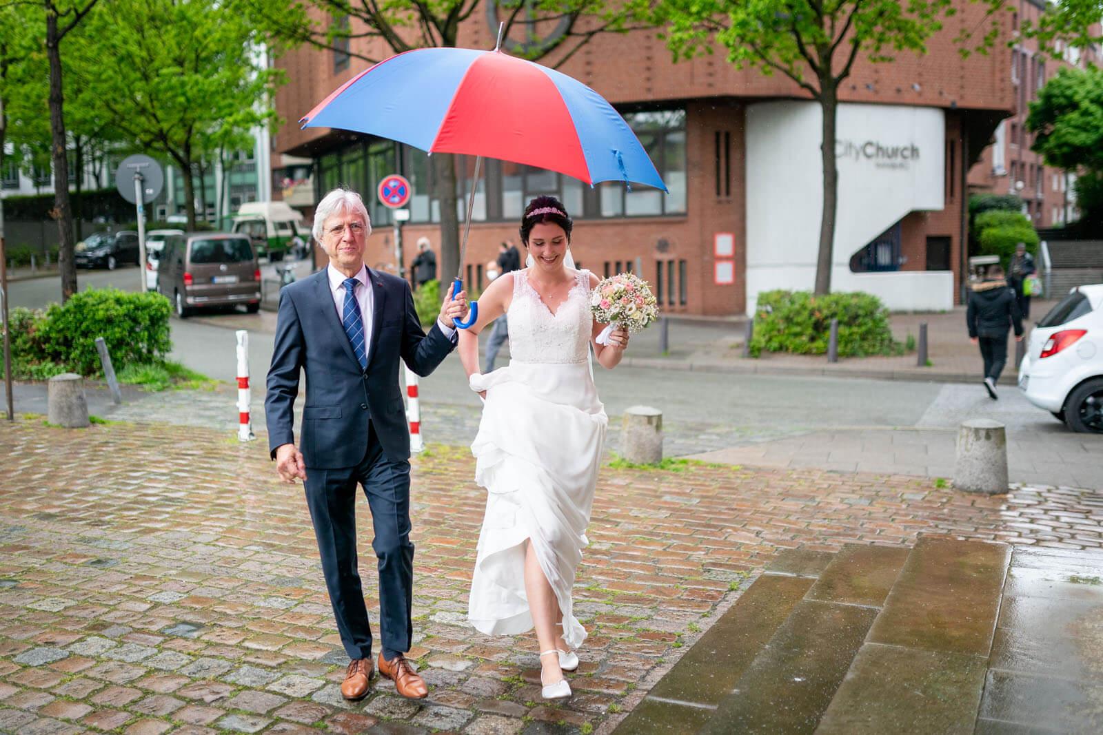 Brautvater begleitet seine Tochter bei Regen zur Kirche.