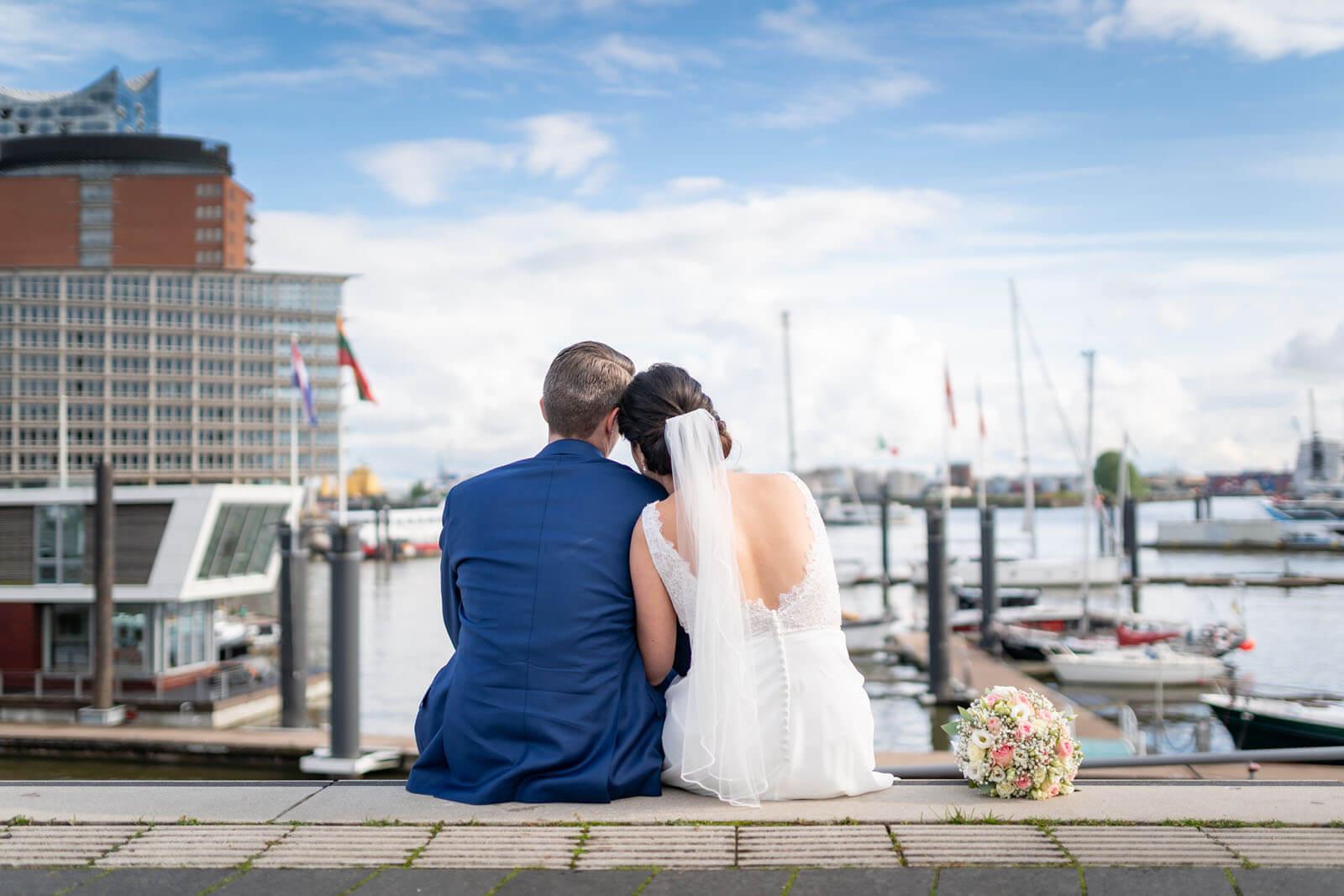 Brautpaar an der Elbe mit Elbphilharmonie im Hintergrund.