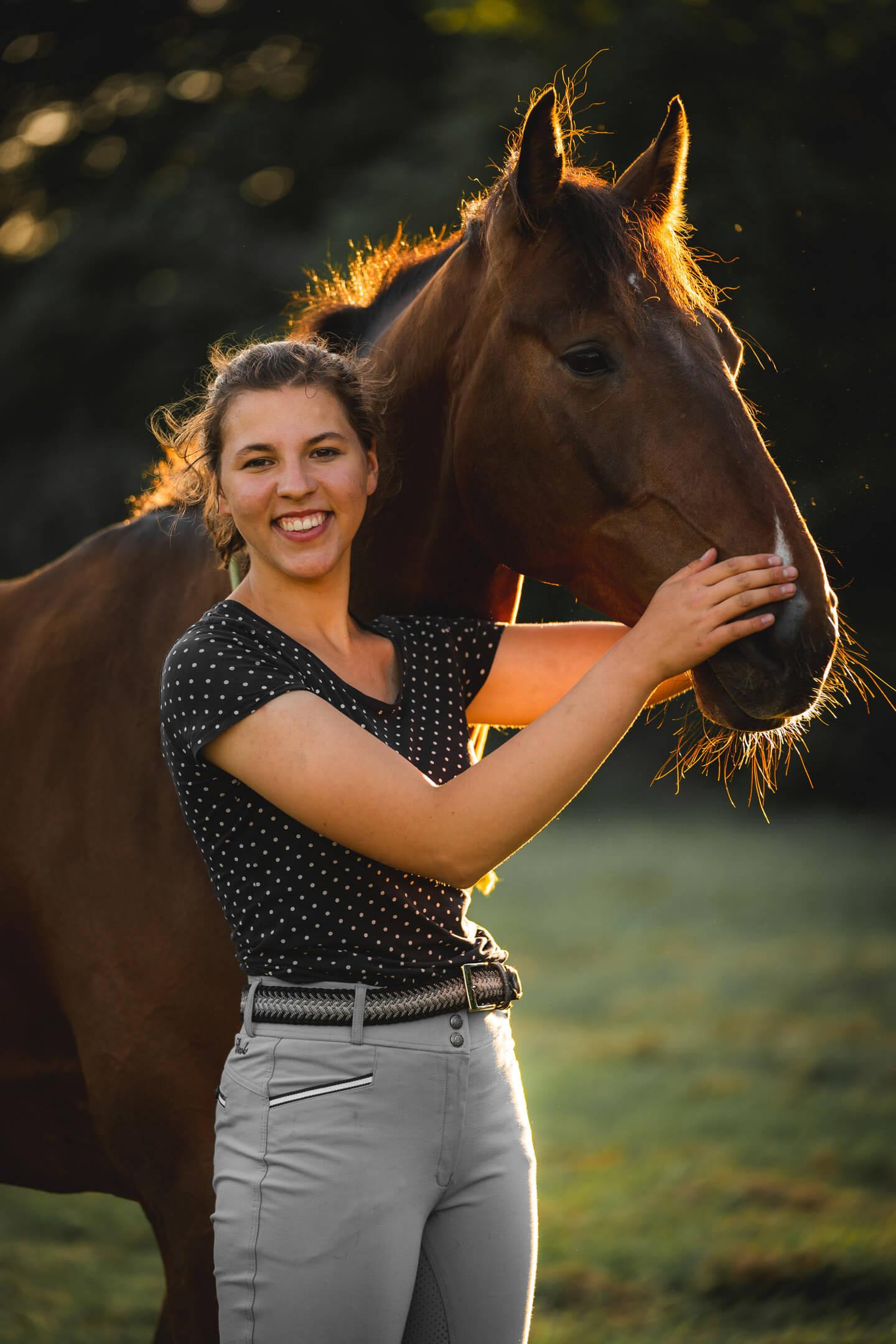 Reiterin und Pferd im Abendlicht fotografiert.