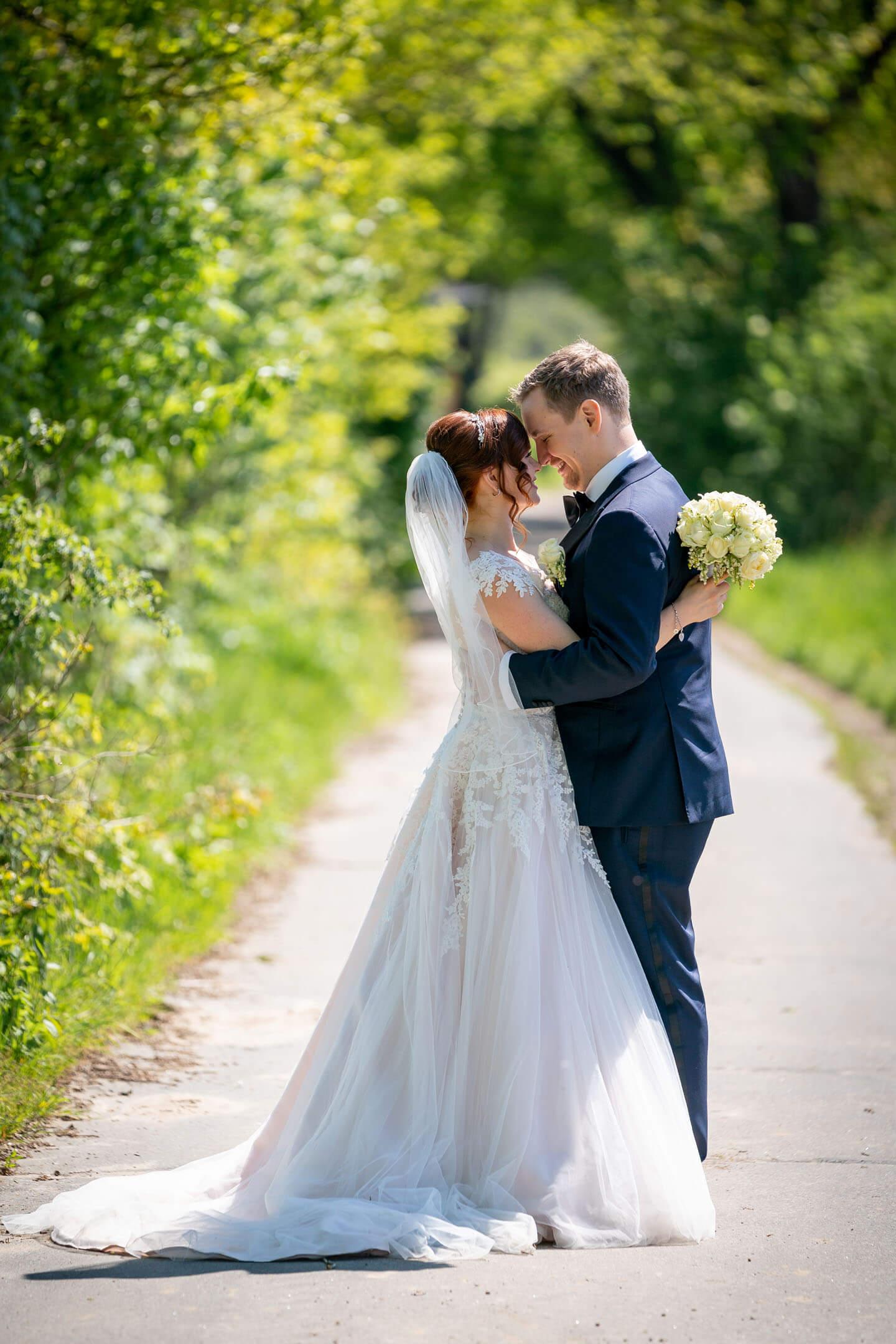 Brautpaar auf einer Baumallee