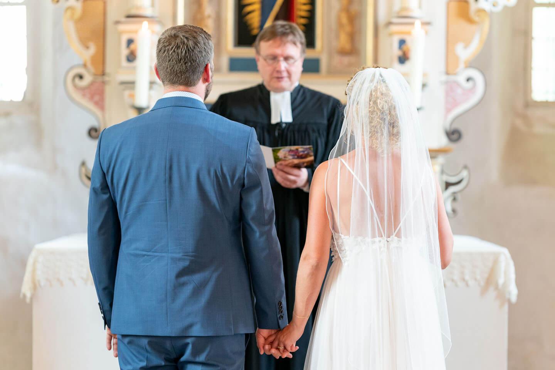 Hochzeitspaar vor dem Altar mit Pastor beim Traugottesdienst