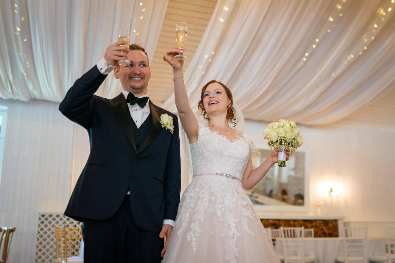 Brautpaar prostet der Hochzeitsgesellschaft mit Champagner zu.
