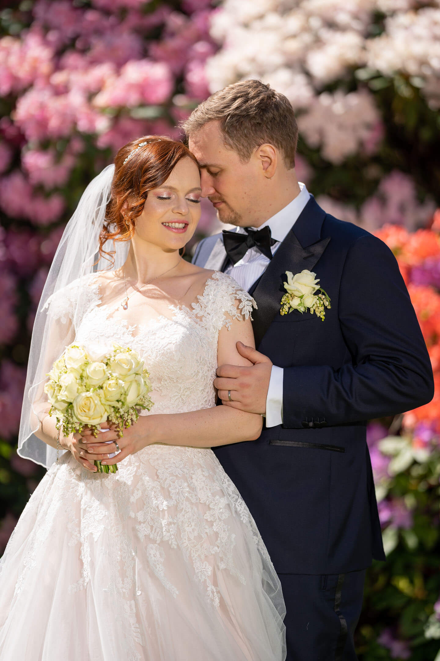 Klassisches Hochzeitsfoto vor blühendem Rhododendron.