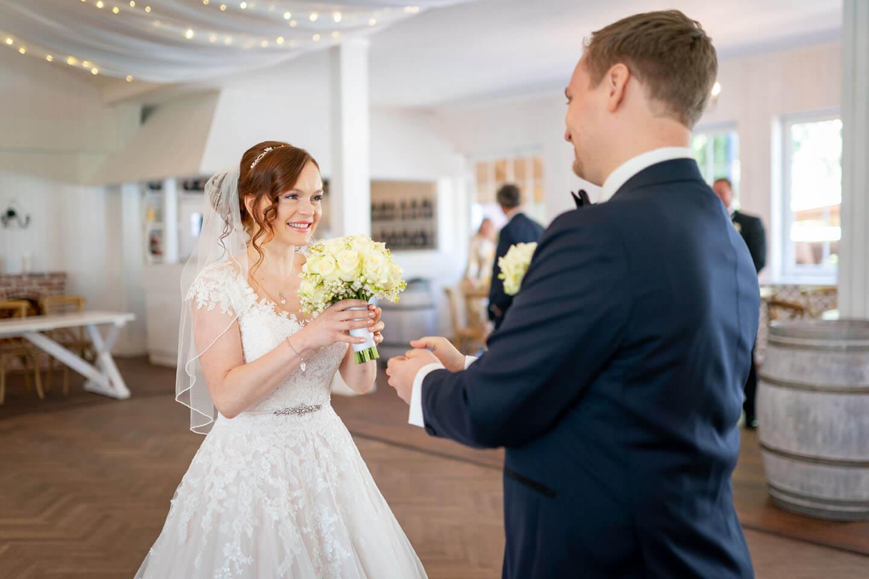 Bräutigam reicht beim first Look Shooting seiner Braut den Brautstrauss.