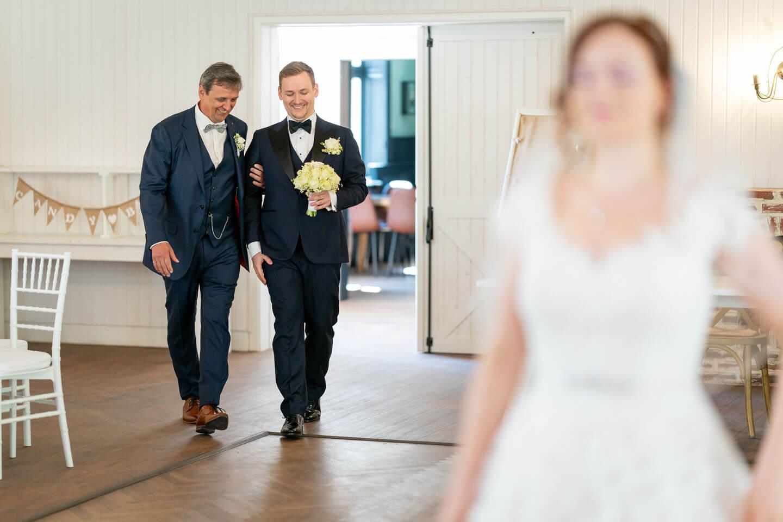 Bräutigam wird in den Saal zum First Look Shooting geführt.