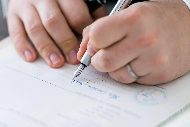 Detailfotos sind bei jeder Hochzeitsreportage wichtig. Hier das Unterschreiben der Heiratsurkunde.