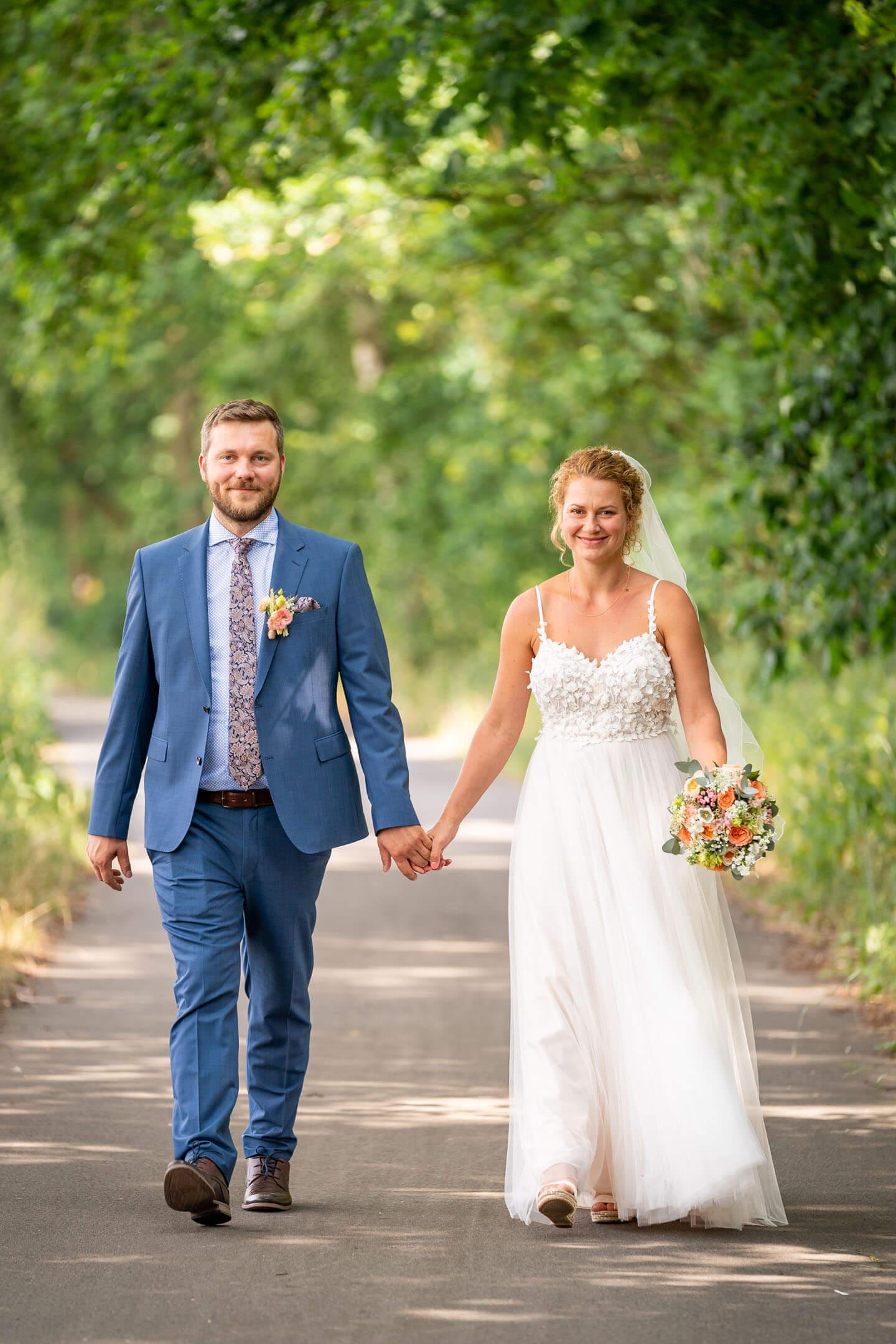 Hochzeitspaar geht Hand in Hand eine Allee entlang