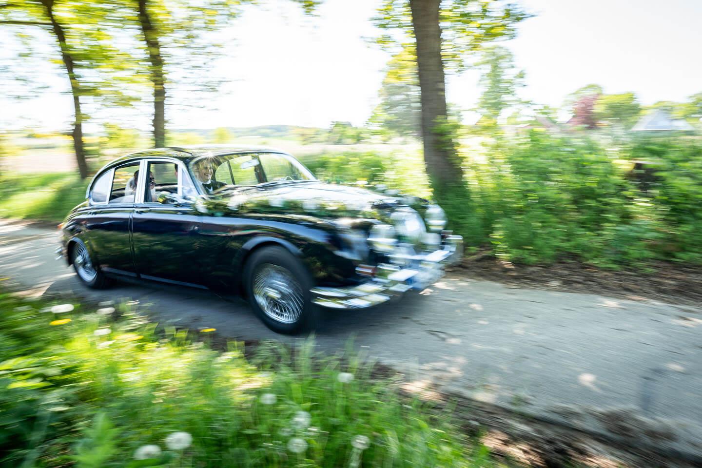 Hochzeitsauto düst durch einen Feldweg.