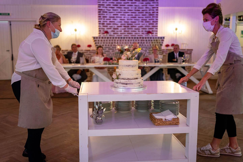 Das Servicepersonal bringt die Hochzeitstorte in den Saal
