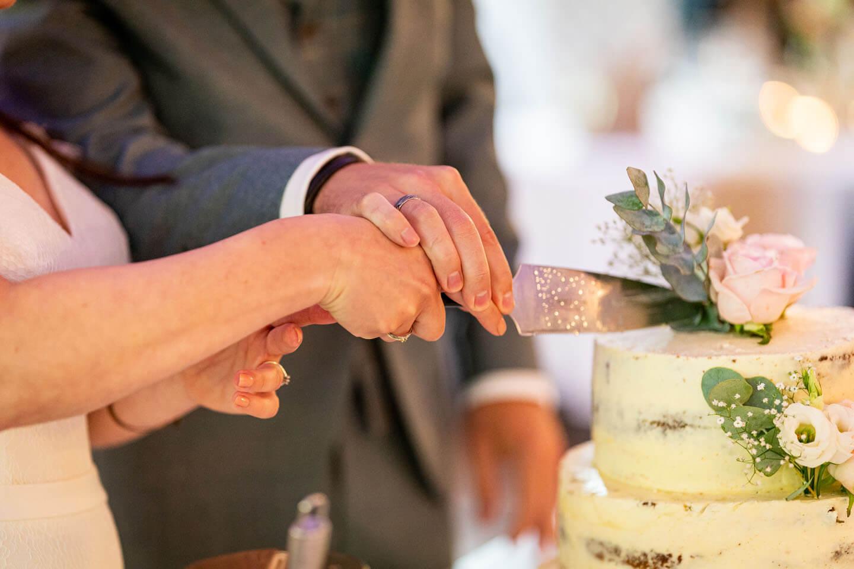 Anschnitt der Hochzeitstorte mit dem Tortenmesser