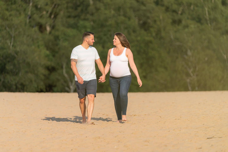Paar geht Hand in Hand auf Sand